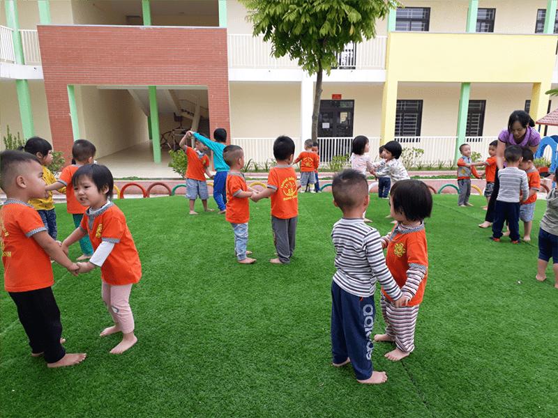 Hai bé đứng đối diện nhau và nắm tay nhau