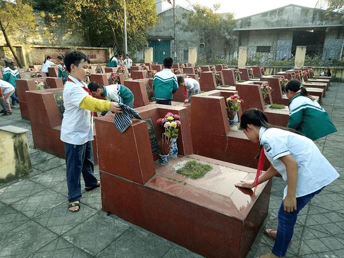 Các em thực hiện làm vệ sinh mộ liệt sĩ tại nghĩa trang liệt sĩ của địa phương